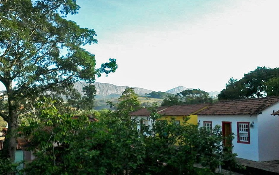 Os chalés da pousada na cidade histórica de Minas ficam cercados de árvores, em um cenário muito charmoso