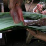 O peixe recém-pescado é enrolado em folhas