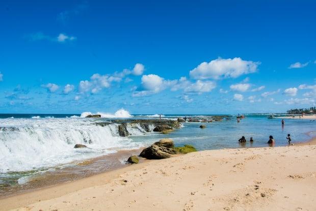 Na praia do centro urbano do vilarejo no litoral norte da Bahia, forma-se uma piscina natural